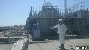 A worker points to a crack in a concrete pit near Fukushima Daiichi's No 2 reactor, 2 April