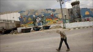 Palestinian boy walks by separation barrier in Aida Refugee Camp, near Bethlehem.