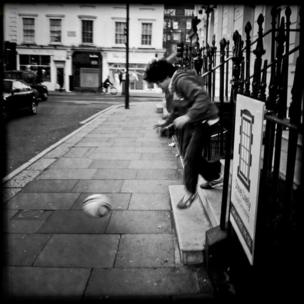 A boy playing with a football in the street
