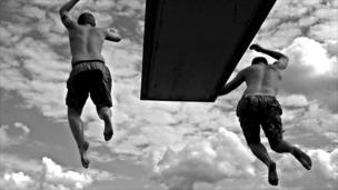 Two young men jump off a diving board