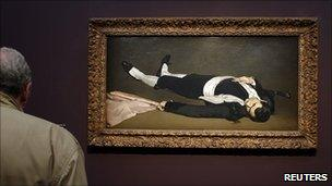 A visitor looks at the painting L'Homme mort 1864-65