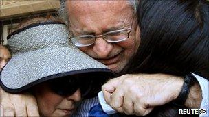 Mexican writer Javier Sicilia cries as he hugs family members after the death of his son