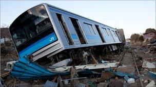 A wrecked train sitting on the ground amid tsunami rubble in Japan