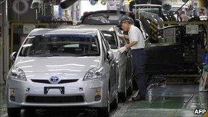 A factory worker checking an assembled car