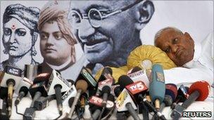 """Social activist Anna Hazare rests near microphones of news channels during a """"fast unto death"""" campaign in New Delhi April 8, 2011."""
