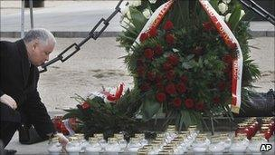 Jaroslaw Kaczynski sets down a candle for his brother Lech at a makeshift memorial in Warsaw