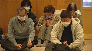 Homeless survivors pray at Kamaishi's temple