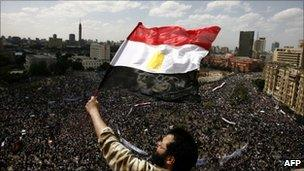 An Egyptian protester waves his national flag as tens of thousands gather for a demonstration at Cairo's Tahrir Square on April 8, 2011
