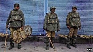 Indian paramilitary soldiers stand in front of shuttered shops during a strike in Srinagar on 11 April 2011