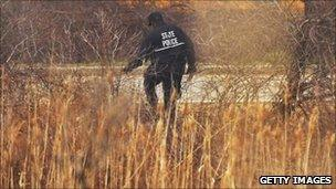 A police officer searches an area near a crime scene on Long Island where the additional remains were found