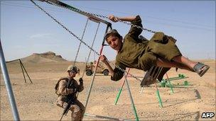 Female Nato soldier watches a boy on a swing in Helmand province of Afghanistan