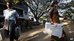 Polling officials carry electronic voting machines to a booth on the eve of elections in Madras (Chennai) on 12 April 2011