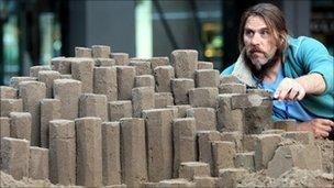 Paul Hoggard shapes his sand sculpture of the Giant's Causeway in Belfast
