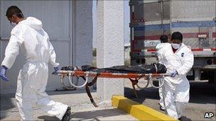 Morgue employees take a body to the local morgue in Matamoros