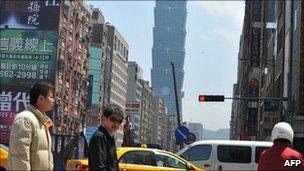 Pedestrians walk in Taipei on April 6, 2011