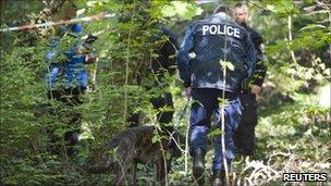 A Zurich policeman walks through the forest with his sniffer dog in Tolochenaz near Morges April 14 , 2011, after Vaud Police organised a search operation from Morges to St-Prex.