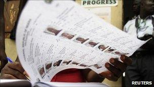 Electoral officer crosschecks names on a voters' register before the start of parliamentary elections in Surulere district in Lagos, Nigeria, on 9/4/11