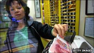 Currency exchange owner counting out Chinese yuan