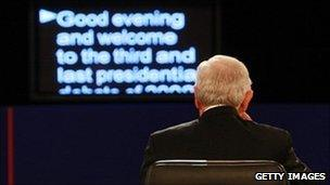 A man sitting in front of a teleprompter