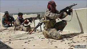 Afghan border police fire at the Taliban forces from a rooftop during clashes in Kandahar city (8 May 2011)