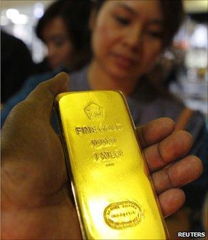Man holding a gold bar at an Asian trade fair (Image: Reuters)
