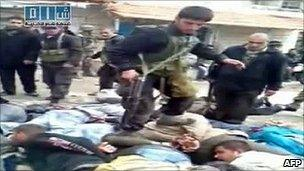 Syrian security officer walking on top of handcuffed anti-government protesters lying on the ground in Baida (Sham SNN opposition web channel, 14 April 2011)