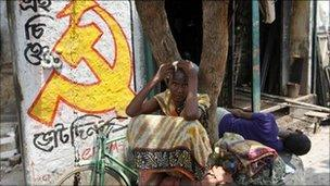A woman sits under a tree next to a logo of the Communist Party of India (Marxist) in Kolkata in this May 11, 2011 file photo.