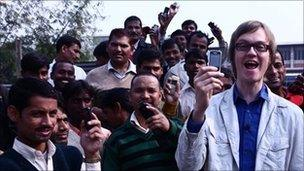 Alex Riley and Indian men hold phones