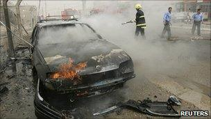 Firefighter hoses down burning vehicle