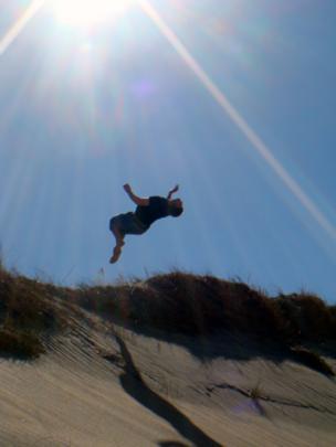 Man doing a back flip on sand dunes