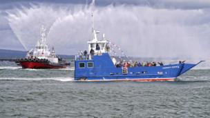 Ferry and tug with water cannons at the launch of the new Cromarty to Nigg ferry