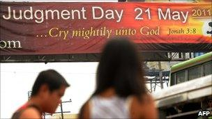 "Pedestrians walk past a banner with a message that reads ""Judgement Day May 21, 2011"" at a street in Manila on 21 May, 2011"