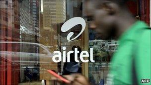 Man in Nairobi, the capital of Kenya, walking past a shop owned by Indian phone firm Airtel