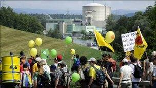 People walk by the Beznau nuclear power plant, the oldest in Switzerland, during an anti-nuclear protest march on 22 May 22, in Doettingen