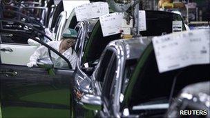 A worker assembles cars at Honda Motor's factory