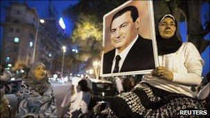 Woman supporter holds a poster of Hosni Mubarak in central Cairo