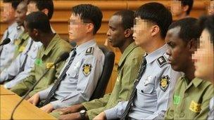 Somali pirates wearing green prison uniforms sit together with South Korean security guards as hearings begin at a court in the southern port city of Busan