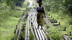 A woman walks along an oil pipeline near in Warri, Nigeria (Archive photograph - 2006)