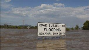 A flooding sign is seen partially submerged in floodwaters in Rockhampton, Queensland