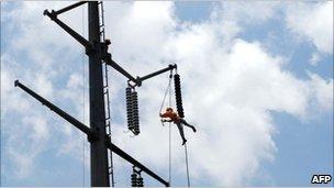 Employee of the Karachi Electric Supply Company (KESC) fixes a power line