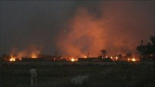 Smoke rises after a clash between farmers and police at Bhatta Parsaul village