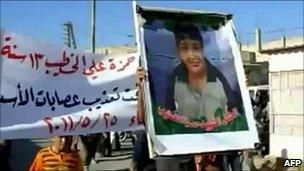 An image grab taken from YouTube on May 28, 2011 showing a protester holding a picture of Hamza al-Khatib