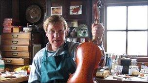 Christoph Gotting holding a violin he made