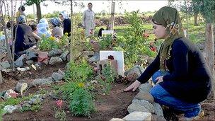 Kurdish women tend the graves of PKK fighters