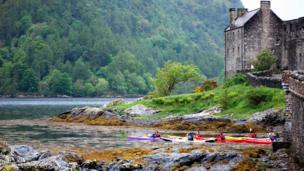 Kayakers in the water by Eilean Donan Castle
