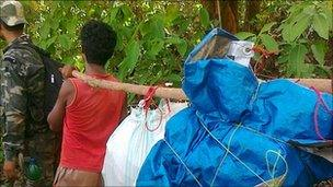 Local people carry the bodies