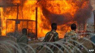 Armed men walk past burning houses in Abyei (28/05/11)