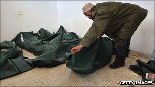 A doctor zips up body bags in Benghazi (25 February 2011)