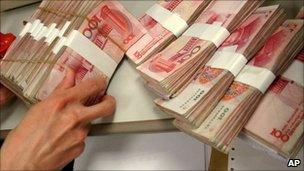 A person handling Chinese yuan bills