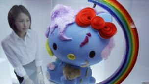 Woman looks at an artwork of Hello Kitty at an event called House of Hello Kitty in Tokyo